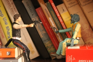 My apologies.  Mr. Battler was too cheap to spring for a doll house table.  Assume Greedo can't see Han's piece, thus giving the rogue pilot the element of surprise.